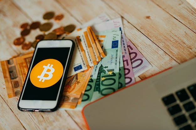phone and money | Investing In Bitcoin FAQs | Inside Your IRA | best way to invest in bitcoin