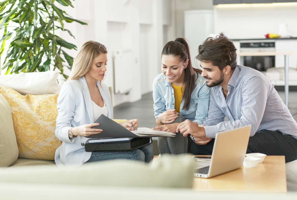 female real estate agent assisting couple   How To Start Investing In Real Estate Inside Your IRA   how to start investing in real estate   real estate investor