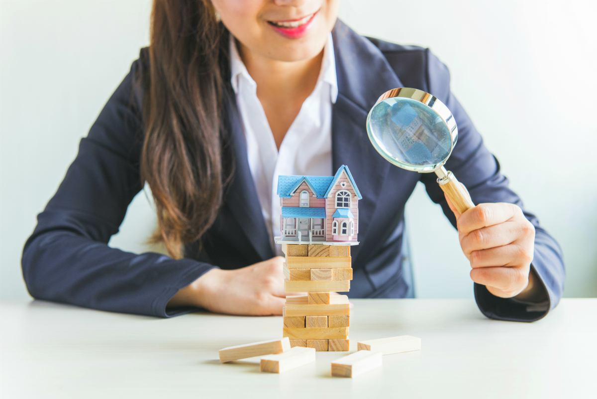 businesswoman holding magnifying glass   How To Start Investing In Real Estate Inside Your IRA   how to start investing in real estate   real estate investor
