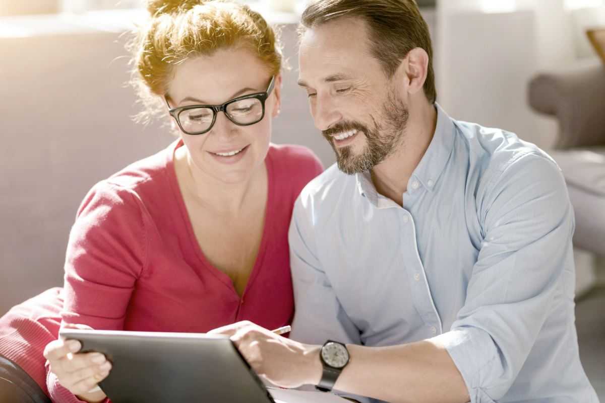 middleaged couple holding tablet | Roth IRA Definition | Terms To Remember Inside Your IRA | Roth IRA definition | Roth IRA accounts