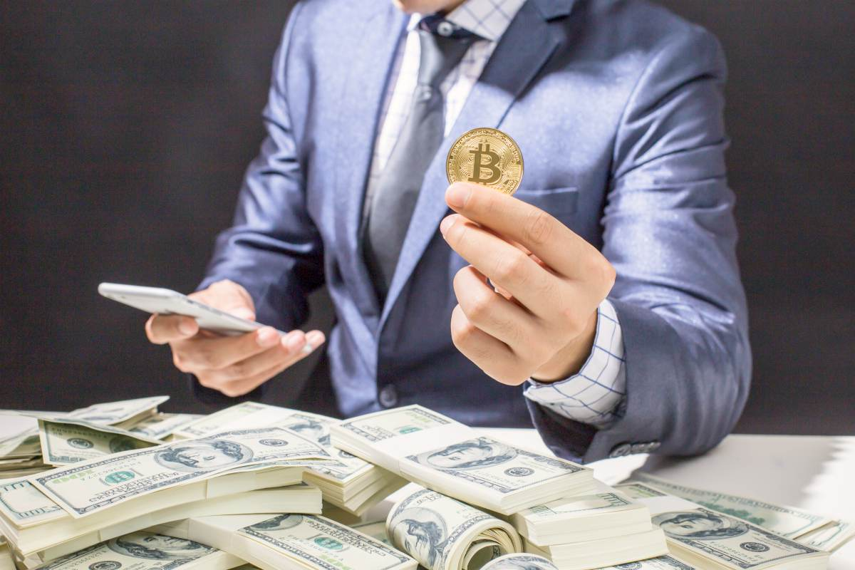 businessman holding bitcoin | What Is Bitcoin And How Can I Invest It In My IRA? | should you invest in bitcoin