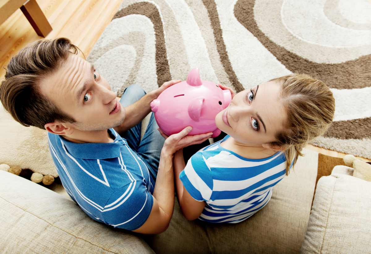 back view of couple sitting in sofa holding piggy bank | How To Start Investing In Stocks: The Ultimate Guide | Inside IRA | investing in stocks | investing in stocks for beginners