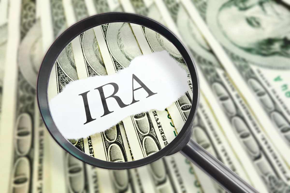 magnified IRA on hundred dollar bills | How To Start Investing In Stocks: The Ultimate Guide | Inside IRA | investing in stocks | investing in stocks for beginners