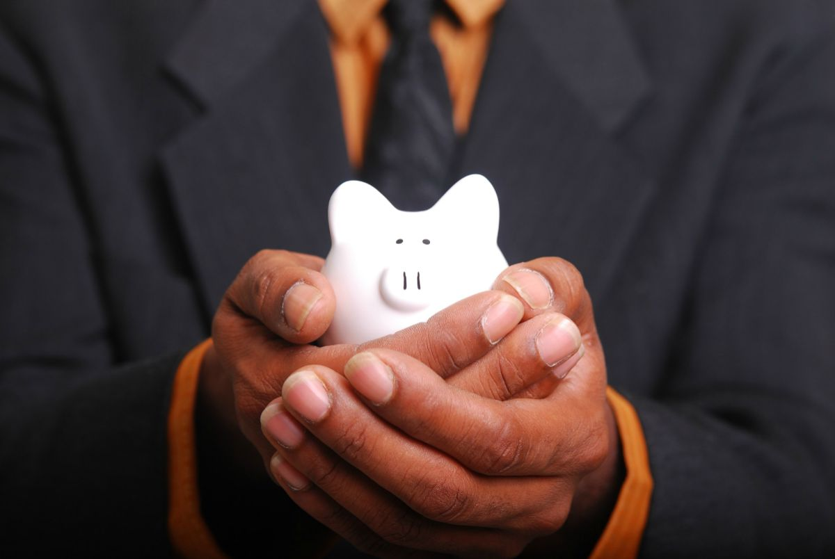 man holding a small piggy bank in his hands | Simple IRA Rules | Everything You Need To Know | simple ira rules for small business