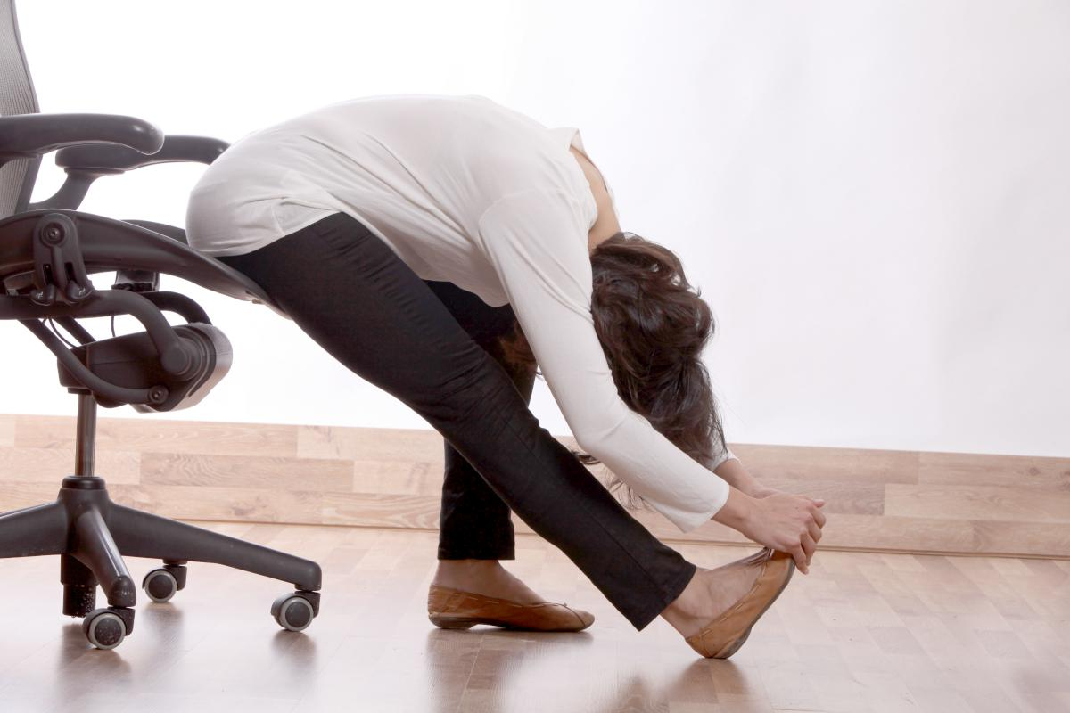 woman stretching at office   Chair Yoga For Seniors   Stay Fit and Flexible Through Retirement   Inside Your IRA   chair yoga for beginners