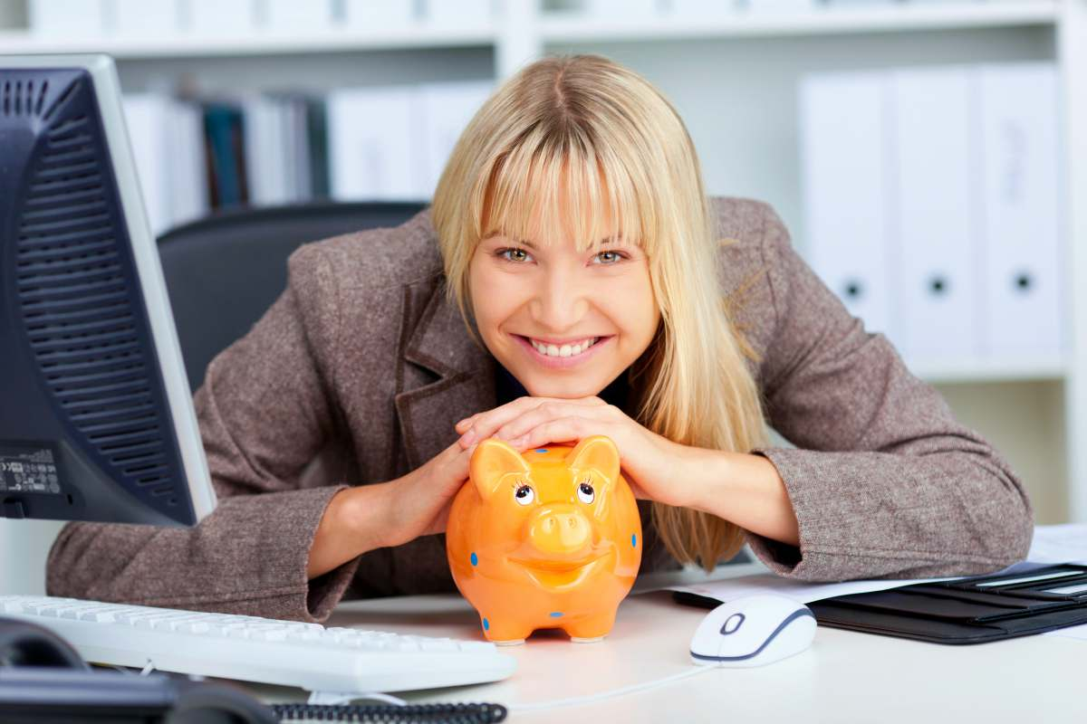 woman smiling with her piggy bank at office | How Does A Roth IRA Work? | Roth IRA Resources | Inside Your IRA
