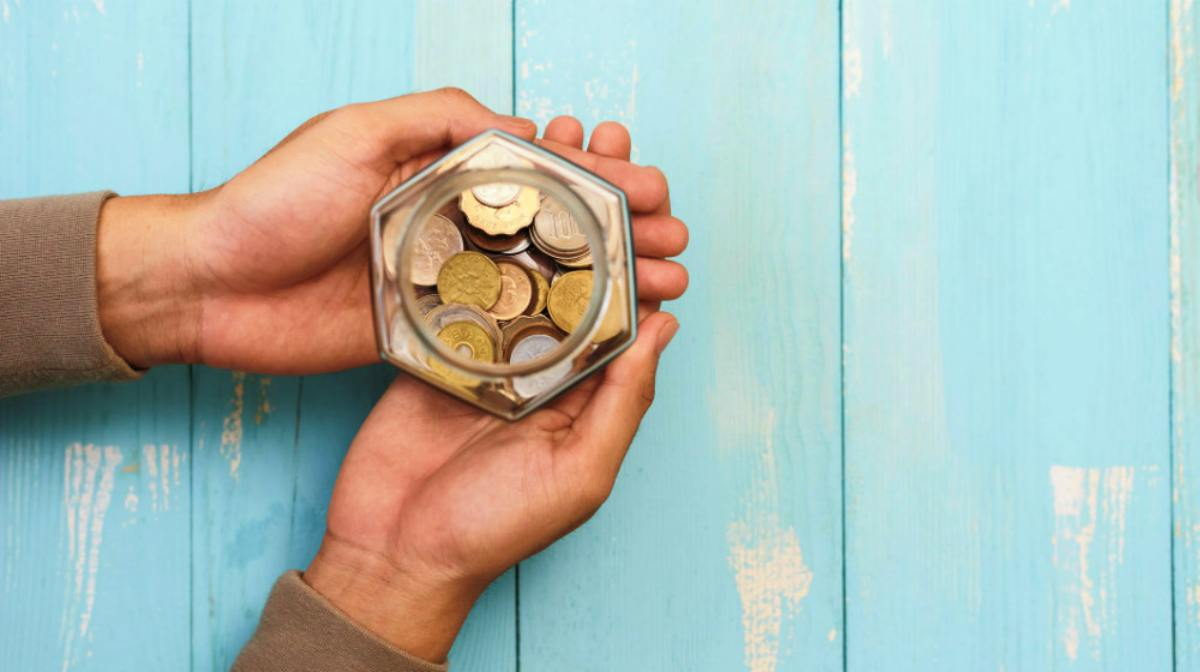 Top shot of hands holding a glass filled with coins | How Does A Roth IRA Work? | Roth IRA Resources | Inside Your IRA