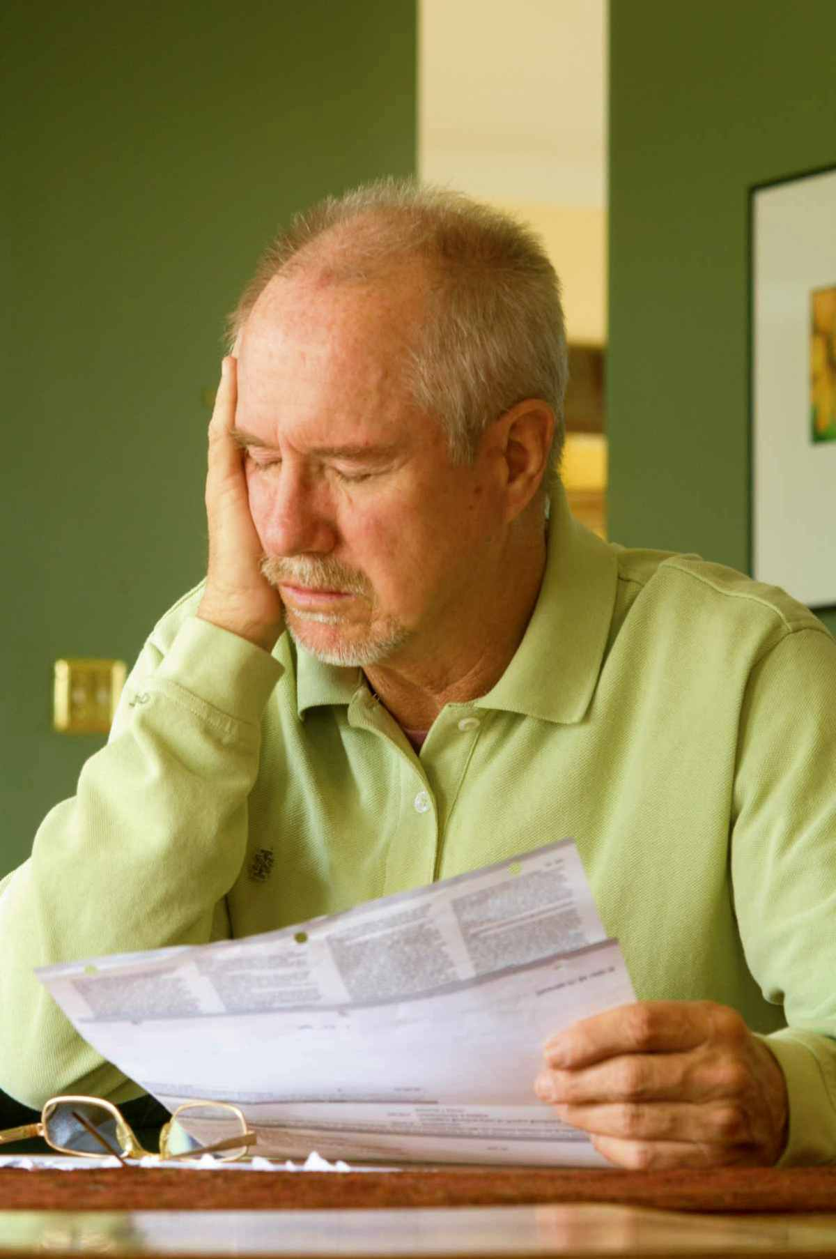 old man worried about bills and documents | What Is A 401(k) vs Roth IRA? | Benefits Of Both Inside Your IRA | roth ira