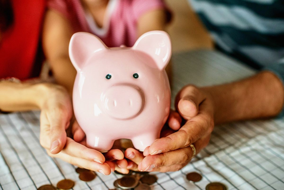 family holding the piggybank on their hand | What Is the Best Way of Teaching Kids About Money? | The Importance Of Teaching Kids About Money | learning the value of money