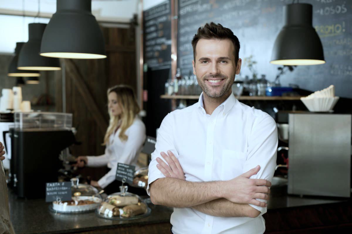 businessman smiling inside a restaurant | Alternative Investments You May Consider | Inside Your IRA | different types of investments