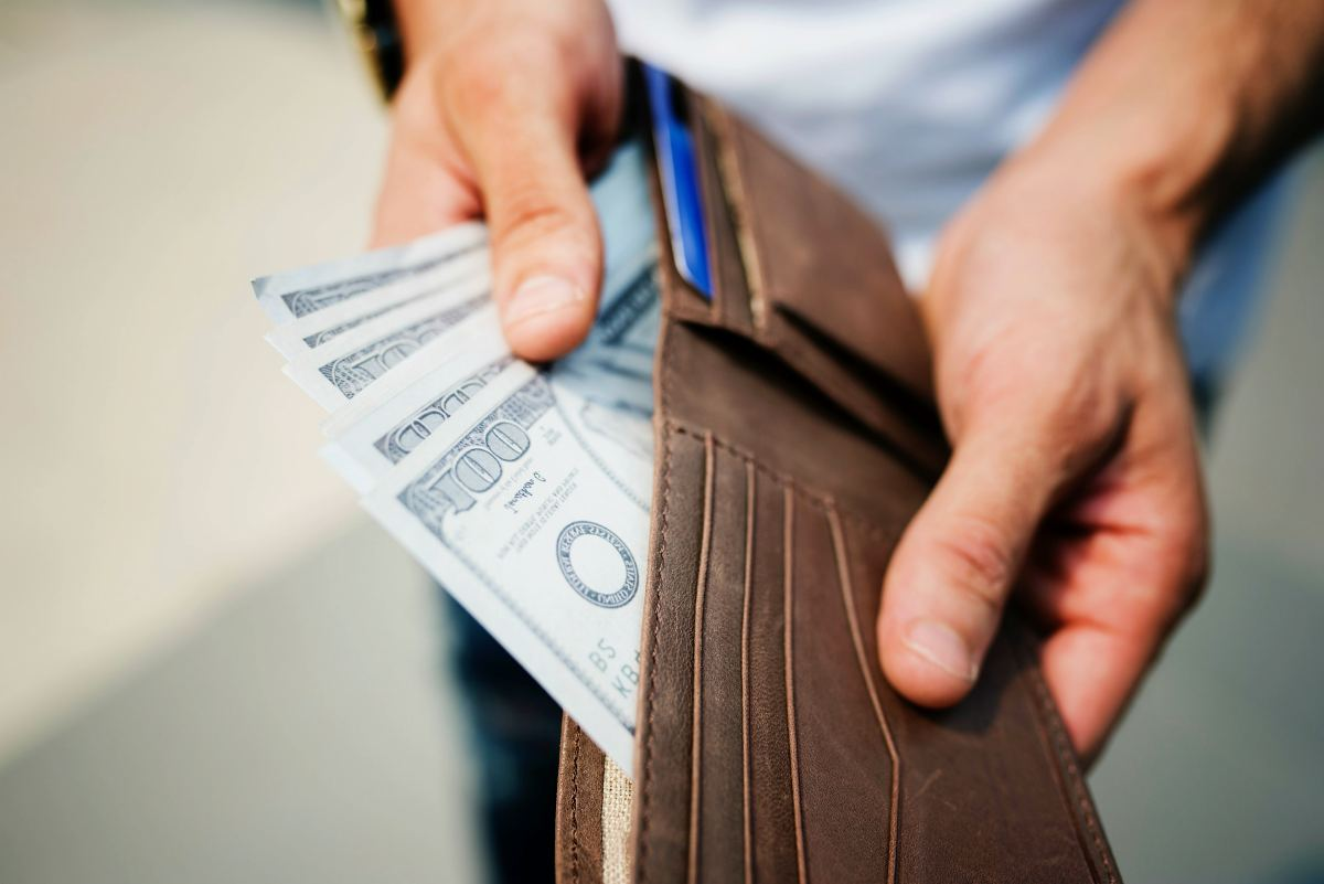 man holding wallet with money | Roth IRA Rules You Most Likely Didn't Know Inside Your IRA