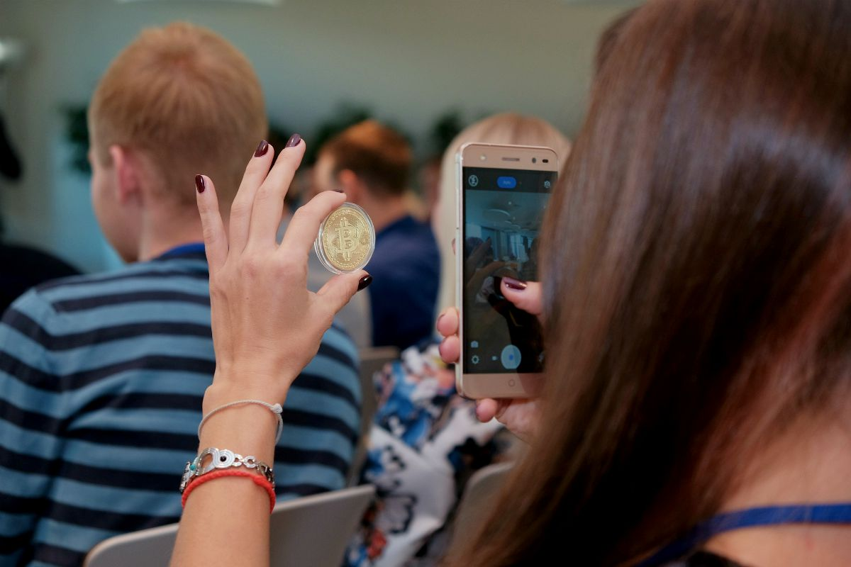 woman taking photo of her bitcoin   USD To Bitcoin: Factors For Change   Inside Your IRA   investing in bitcoin