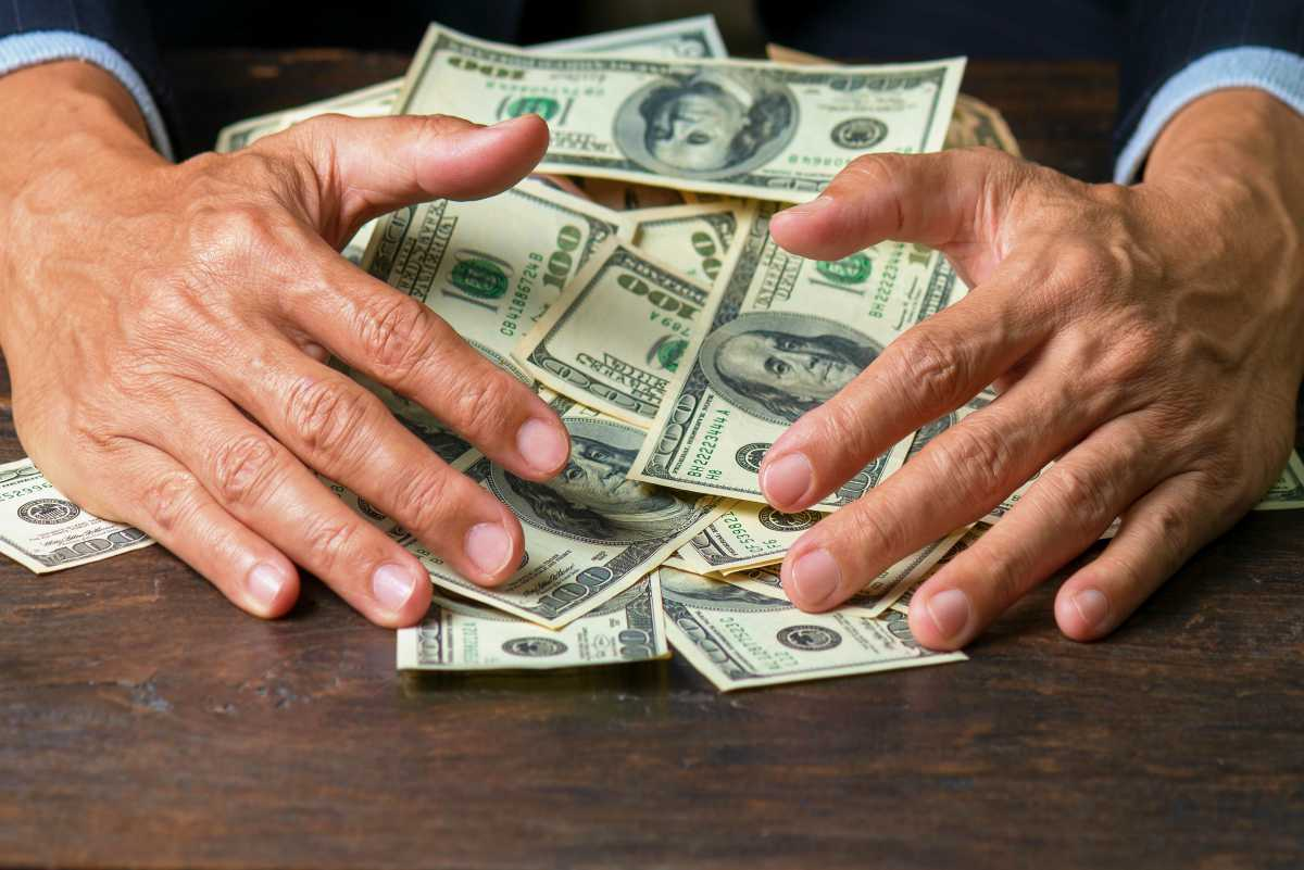 man sweeping money | Marijuana Stocks – What Can You Invest Inside Your IRA? | Inside Your IRA | List of Marijuana Stocks