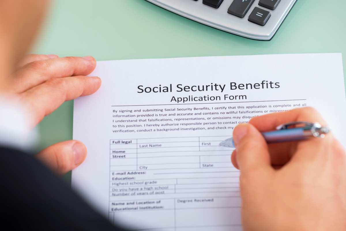 closeup person hand filling social security | Decide When to Apply for Social Security | Retirement