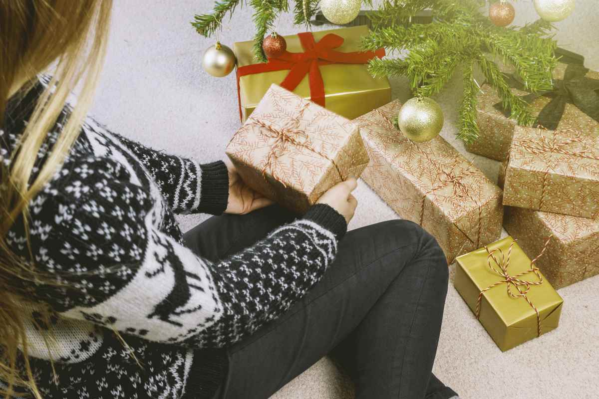 woman in sweatshirt and jeans holding a gift box | Budgeting Tips | How To Stick To Your Budget This Holiday Season | Inside Your IRA | budgeting tips