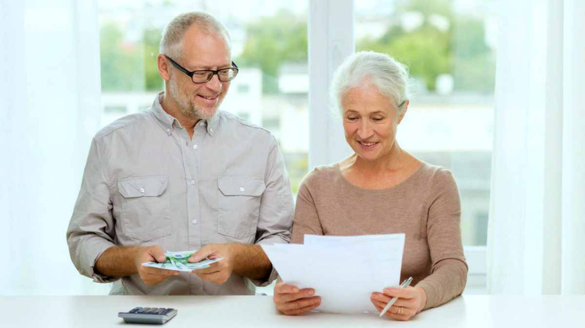senior couple looking at papers and budgeting money | Top Retirement Investments | Inside Your IRA | inside your ira