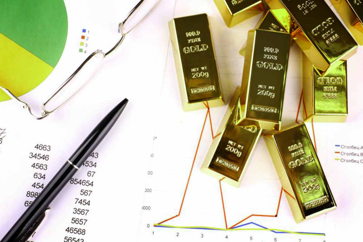 gold bars flat lay paper eye glasses pen and paper with line graph and numbers | Top Retirement Investments | Inside Your IRA | ira