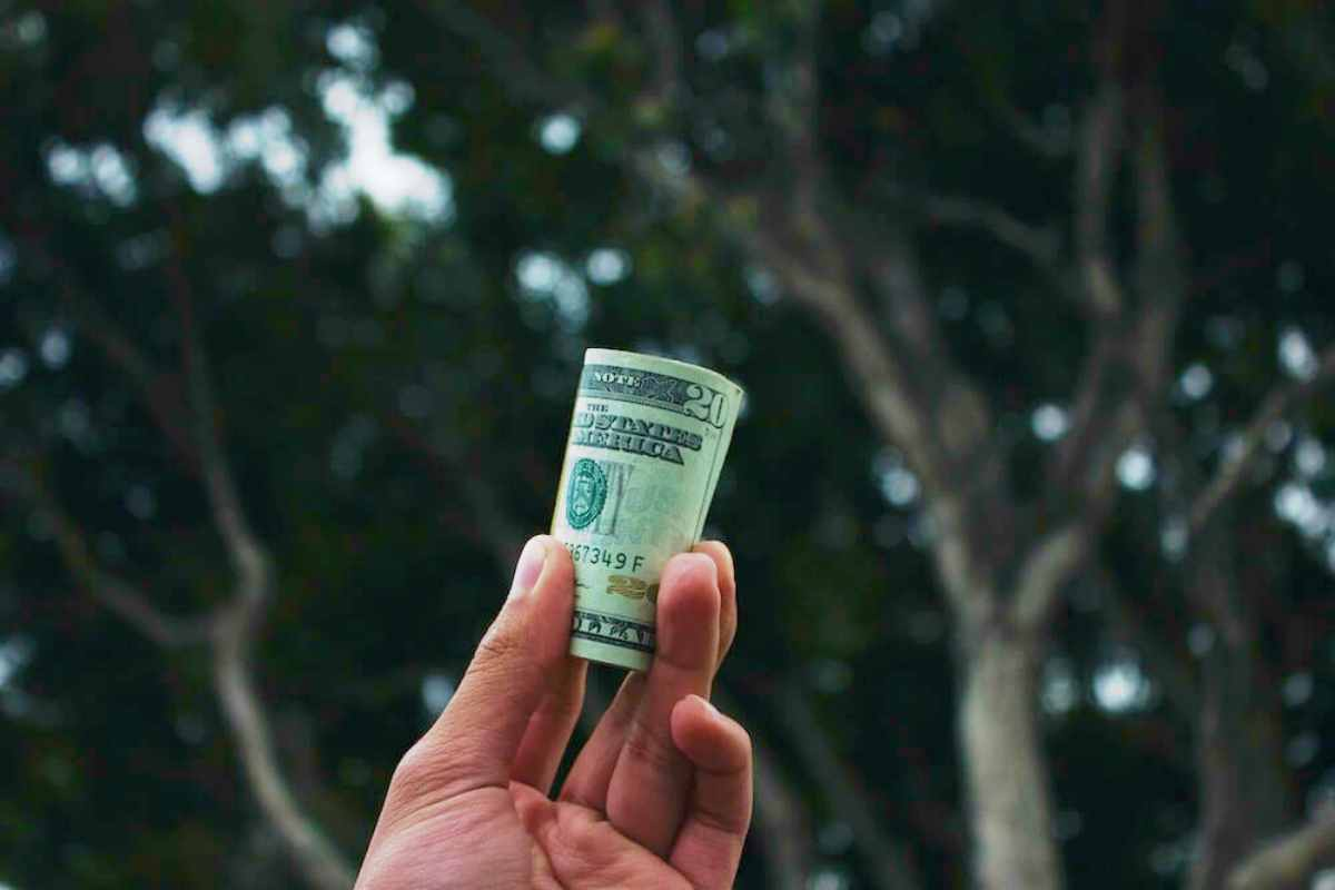 hand holding dollars | Top Retirement Investments | Inside Your IRA | inside your ira