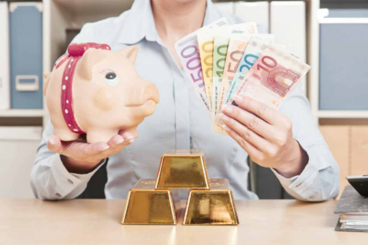 woman holding cash and a piggy bank with gold bars on table | Top Retirement Investments | Inside Your IRA | inside your ira