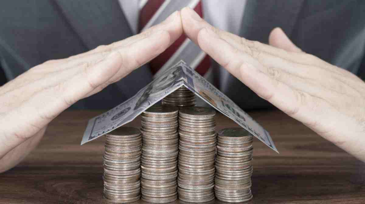 house made out of coins and bill and hands | Top Retirement Investments | inside your ira