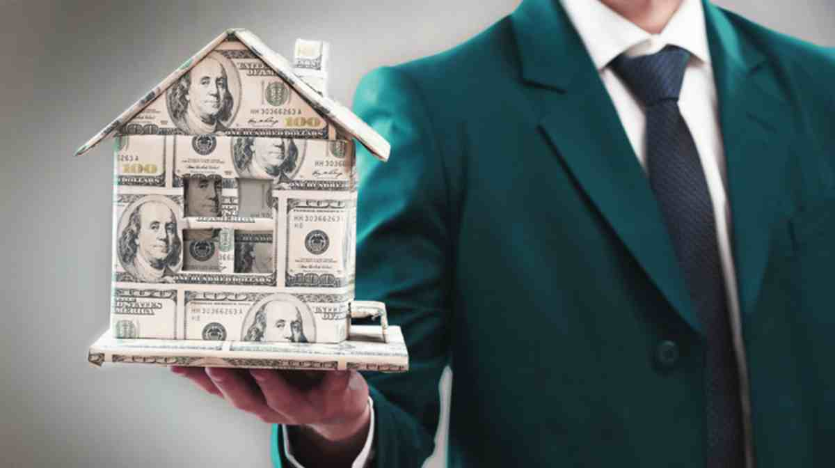 man in coat holding a house made out money | Top Retirement Investments | Inside Your IRA | retirement