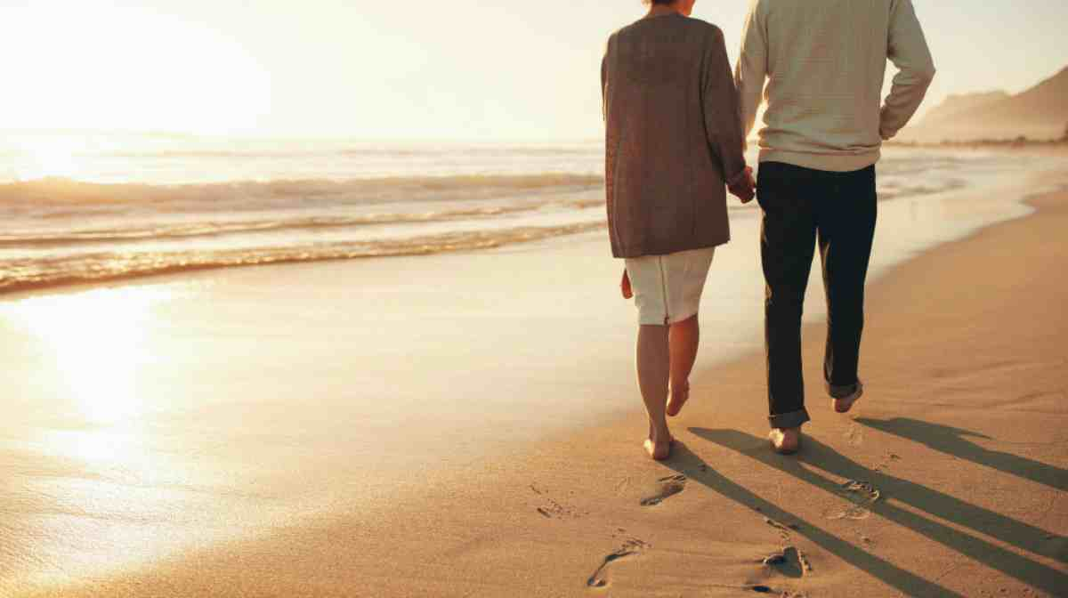 couple holding hands walking together by the beach during sunset | Top Retirement Investments | Inside Your IRA | ira