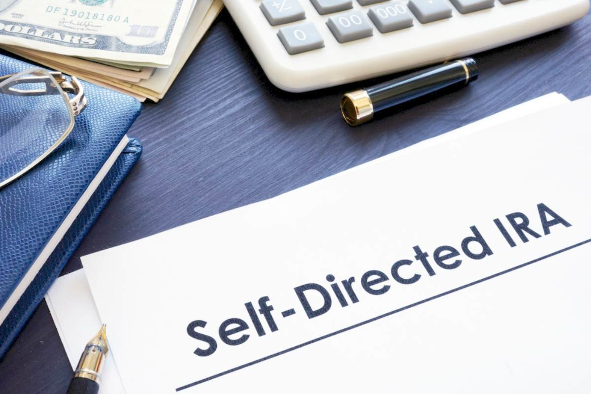 selfdirected ira sdira documents on desk | Investment Ideas | Investing With Little Money | Inside Your IRA | best investment ideas