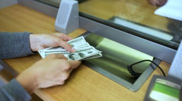 Feature | person withdrawing money | How To Avoid A Withdrawal Penalty Inside Your IRA | Medical Expenses