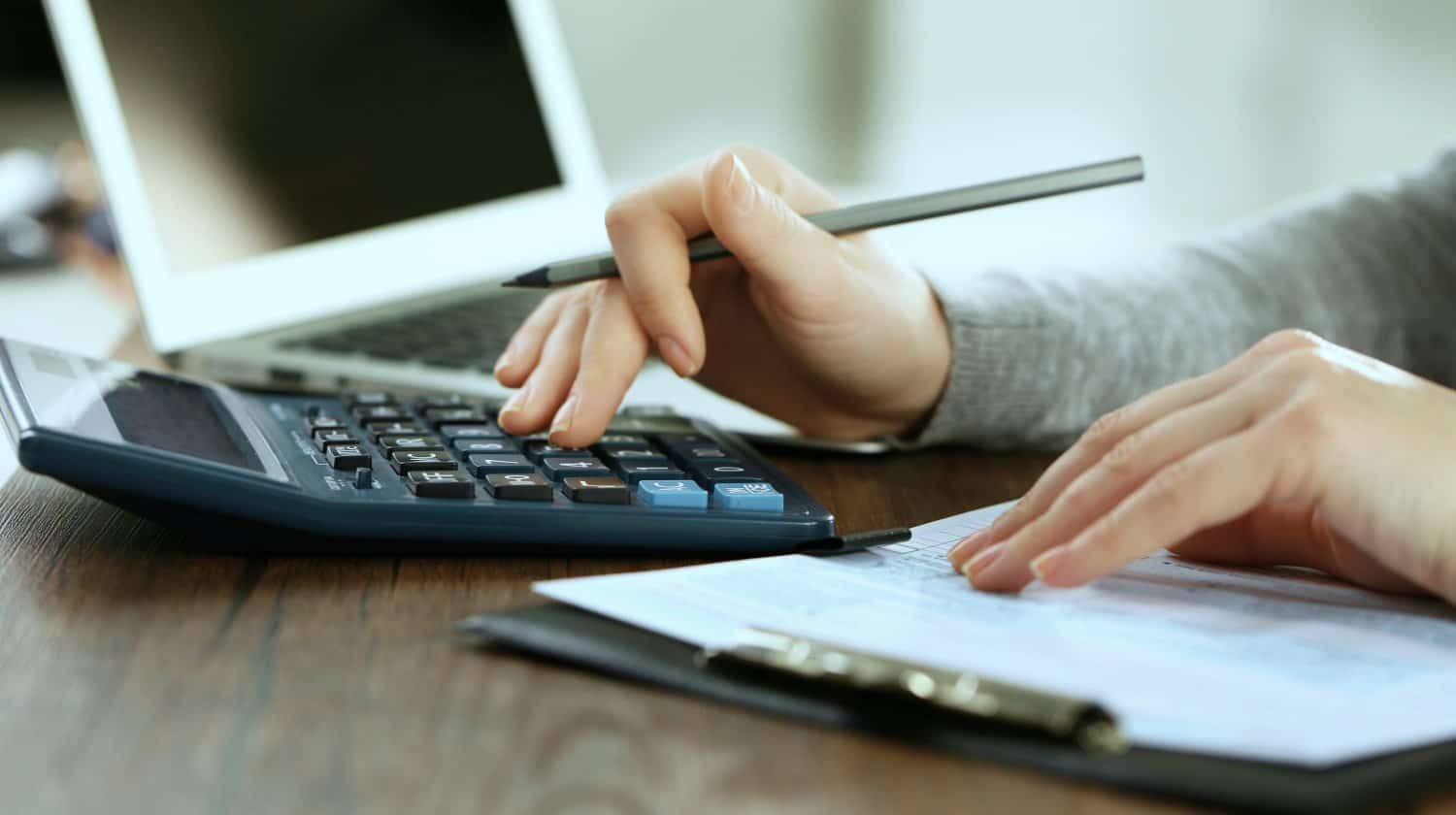 Featured | female hand holding pen and calculator | A Complete Guide To Calculating Roth IRA Basis | Inside Your IRA | what is roth ira basis