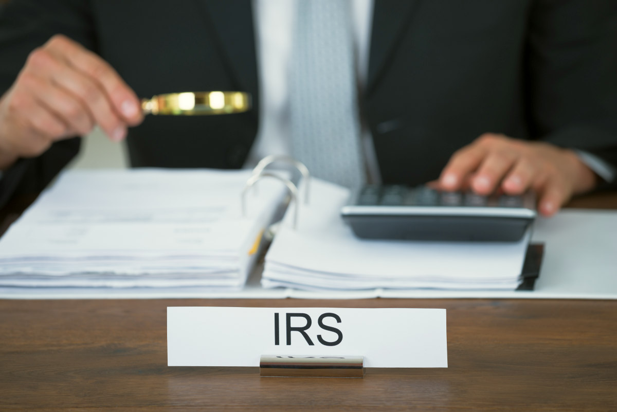 Midsection of tax auditor examining documents with magnifying glass | Roth IRA Tax Deductions, Issues And Withdrawal | Inside Your IRA | Roth IRA Tax Deduction