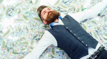 Featured   Business man lying in banknotes   How To Become A Millionaire with Roth IRA   Inside Your IRA