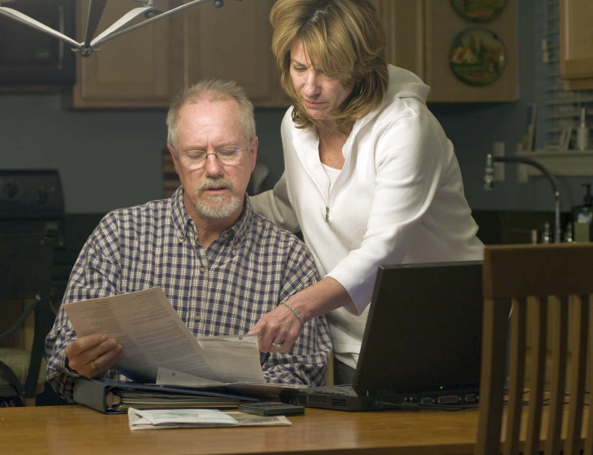 Couple read financial statements at home | Roth IRA Tax Deductions, Issues And Withdrawal | Inside Your IRA | Roth IRA Tax Deduction