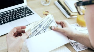 Featured   man counting money from an envelope   self directed ira fees   What Are Self Directed IRA Fees? Checklist Template