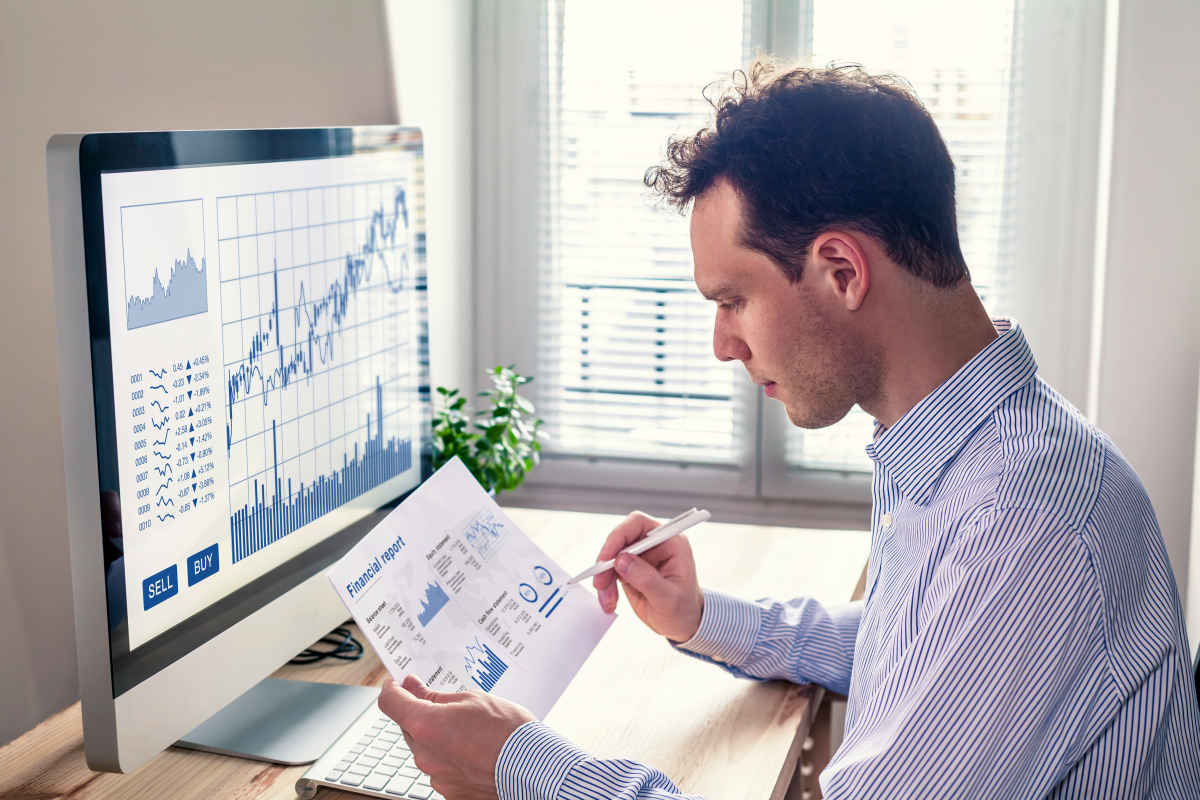 Trader analyzing financial report and trading charts | What Is The Future Of Cryptocurrency?