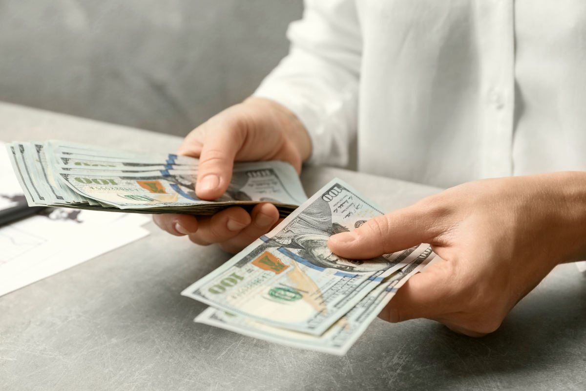 Woman counting dollars at table | Roth IRA Tax Deductions, Issues And Withdrawal | Inside Your IRA