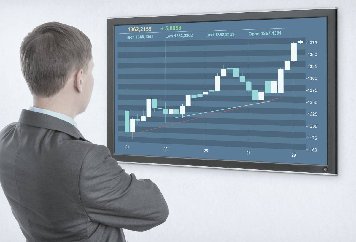 man looking at tv monitor | What Does The Gold-Silver Ratio Mean In Your Portfolio? | Inside Your IRA | gold silver ratio | gold silver ratio chart